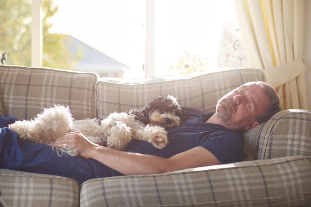 man sleeping on sofa with his dog