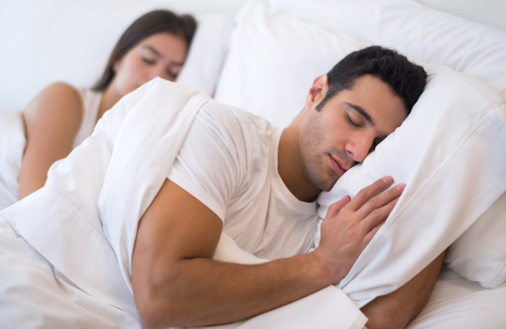 man lying on bed looking comfortable