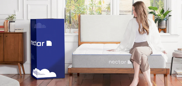 woman sitting on mattress with nectar brand packaging the background