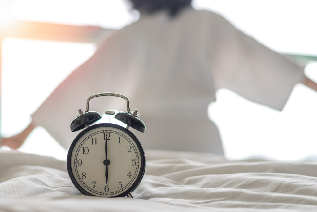 alarm clock sitting on bed while woman stretches in the background