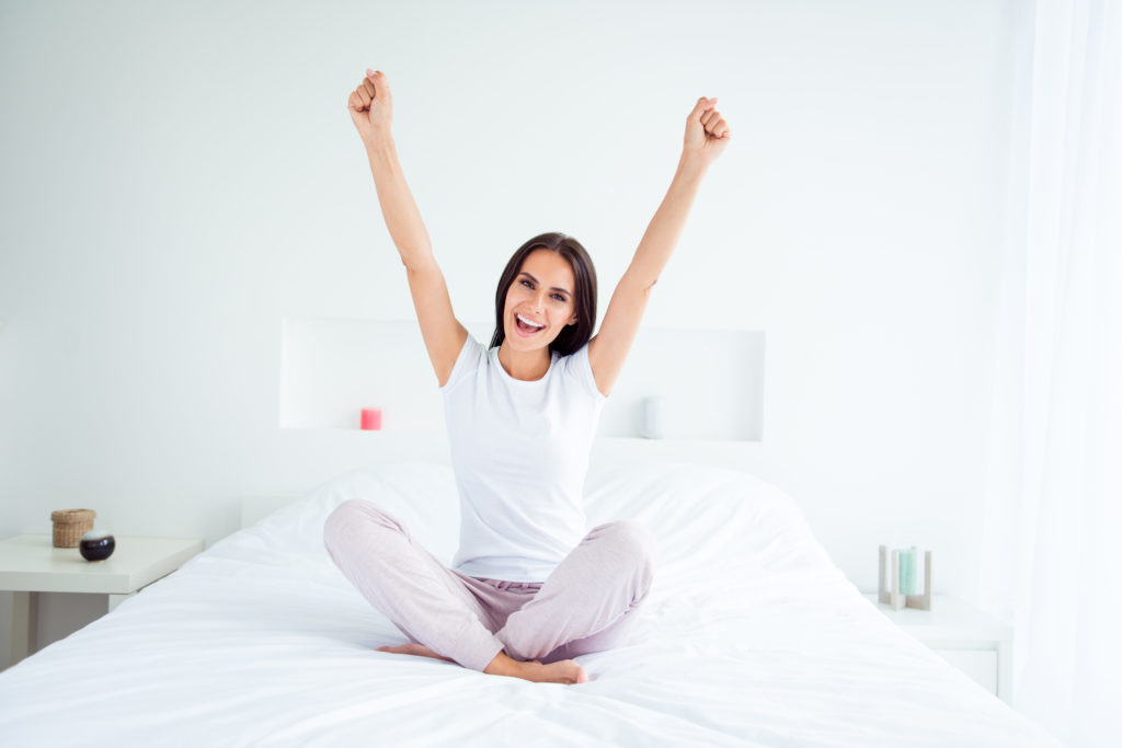 young caucasian woman sitting on bed looking happy and arms in the air