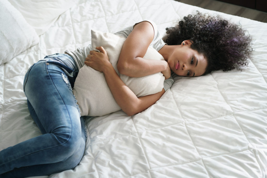 young african american girl lying down on bed and holding pillow looking depressed