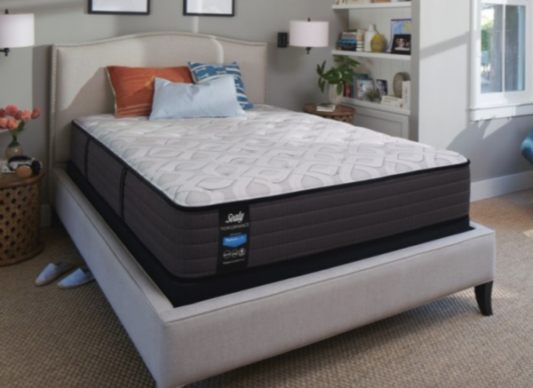 black mattress with white top on beige bed frame