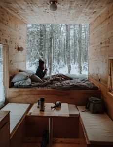 Image of a small room woman in bed drinking coffee looking out into the forest in winter