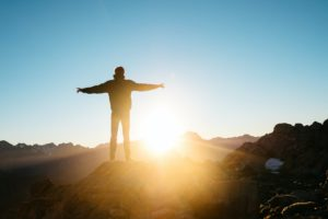 Image of man with outstreched arms looking at the sunrise on the mountains