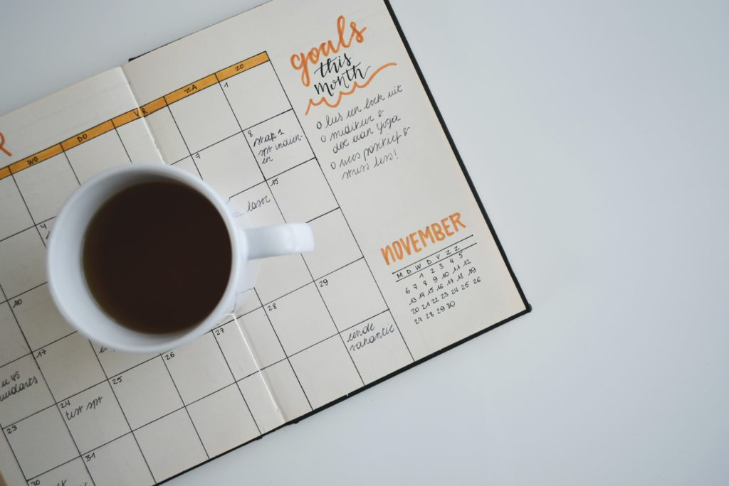"""Image of paper calendar with """"goals"""" written on it and a coffee cup"""