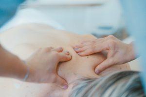 Massage in progress. Two hands massaging someones shoulders