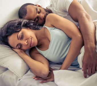Beautiful young couple is sleeping in their bed at home