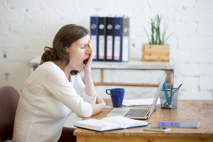 young woman sleep-deprived, sitting at table in front of laptop, sleepy, tired, overworked