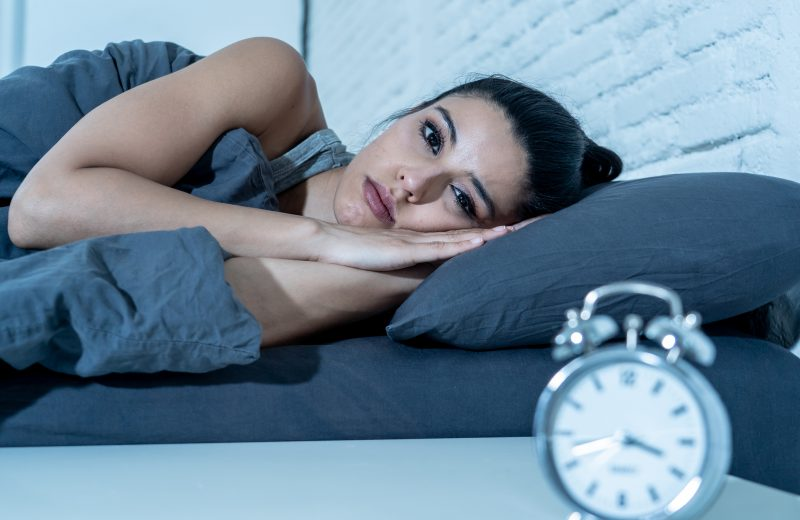 woman lying in bed looking at clock unable to sleep