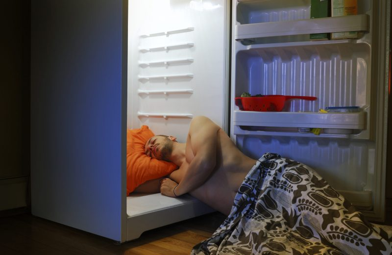 man laying on floor paritally in fridge to cool down