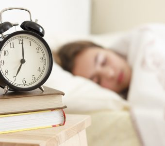 woman sleeping with focus on alarm clock in front of her on night stand