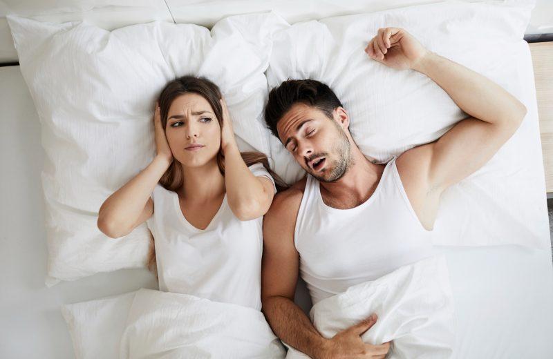 woman lying awake next to snoring husband