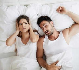 woman lying awake next to snoring husband