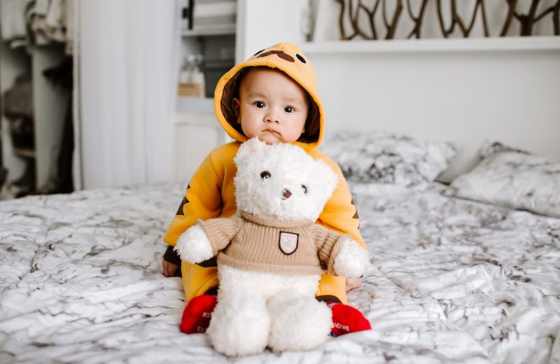 Child in raincoat sitting on bed holding teddy bear