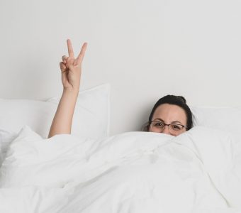 image of woman in bed with white sheets and throwing a peace sign