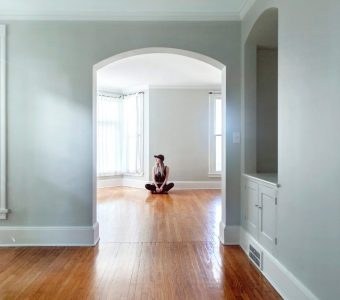 Woman sitting on the floor in an empty room of a house