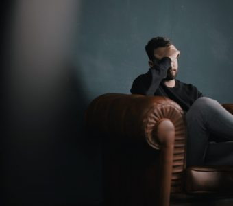 Image of man on a leather chair holding his hand over his brow