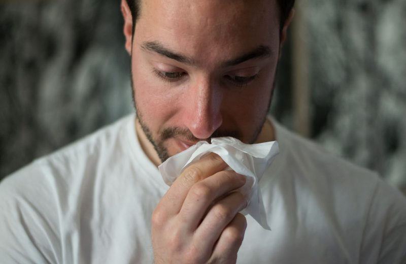 Man wiping face with tissue due to allergies that could be solved from a hypoallergenic mattress